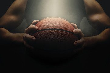 Male basketball player with a ball over dark background. Low light. Fit young man in sportswear holding basketball.