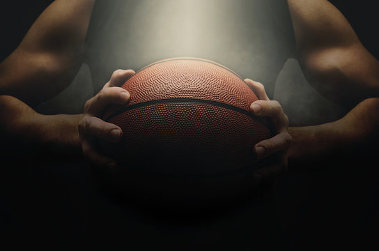 Basketball player with ball over dark background
