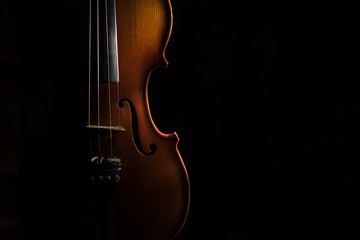 Violin on a black background lit from one side