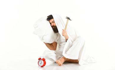 Guy on sleepy face beats alarm clock with hammer.