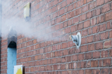 Steam vent from a gas boiler on a brick wall