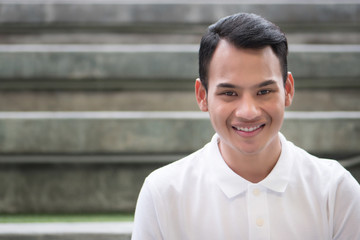 happy man portrait, smiling friendly man, happy handsome man sitting smiling in city environment; young adult south east asian man model with tan skin and short hair