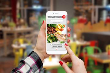 Girl ordering food with smartphone app in restaurant