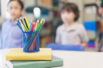 Color pencils in a pencil case at table with kids in library blurred background. concept of education copy space, art and office equipment.