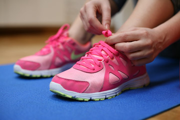 Woman tying the shoelaces of her fitness shoes.
