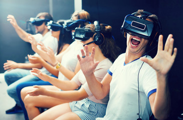 Excited  man experiencing with friends virtual reality