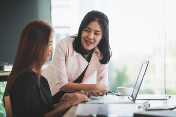 Young Asian women workers working together in office