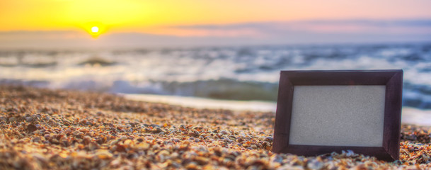 Photo frame on sand background, sea at sunset place for lettering, copyspace