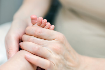 Mother making feet massage for infant baby. Parent care about kid. Children health car and disease prevention