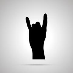 Black silhouette of hand in corna gesture on white
