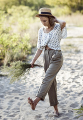 stylish teenager girl in rolled light pants and in a straw hat walks barefoot in the sand in the countryside