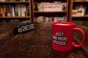 Cup of coffee with inscription Just one more episode and tv remote controller