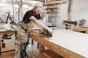 Carpenter working with electric planer on wooden plank in workshop. Craftsman makes own successful...