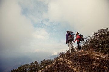 Hikers couple with backpacks relaxing on top of  mountain and enjoying view of valley above clouds
