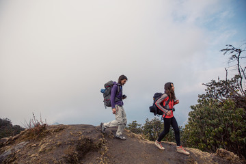 Hikers couple with backpacks walking on top of mountain and enjoying view of valley above clouds