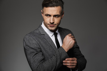 Photo of stylish man wearing business suit looking aside, while fasten cufflink or button on sleeve of jacket, isolated over gray background