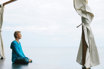 Woman wearing casual close sitting in lotus pose, relaxing and meditate outdoor in ocean shore