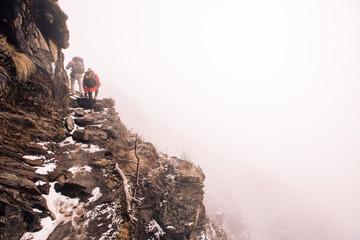 Group of people hikers walking in white fog mountains top on stone steps above clouds and precipice