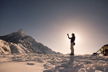 Silhouette of traveller photographer relaxing on top of snow high mountain and enjoying view of Fishtale mountain, sunrise time, strong travel concept