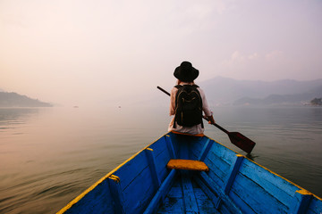Woman wearing black hat and backpack sitting on boat with paddle, nice mountain lake Fewa and sunset on background