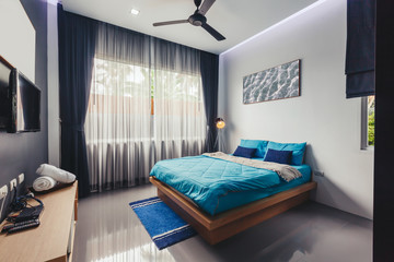 Modern bed room interior in Luxury villa. Big window, fun TV, blue colours