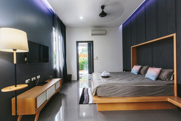 Modern bed room interior in Luxury villa. Big window, fun TV, gray colours