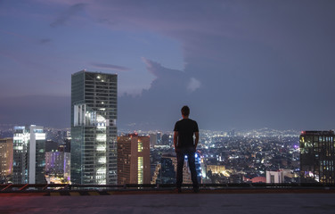 Fotomurales - Men standing on the rooftop Mexico city with night downtown view. Mexico City skyline at night