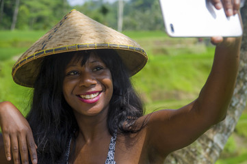 young attractive happy afro american black woman tourist taking selfie portrait photo with mobile phone camera while exploring rice fields forest