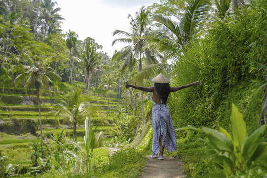 young attractive happy afro american black woman 30s exploring rice fields forest and jungle in Bali wearing rural traditional Asian hat hiking and exploring