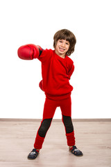 Cheerful boy showing his fist in boxing gloves