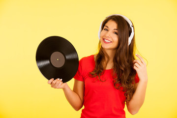 Beautiful young woman in red t shirt listen music over yellow background with copy space