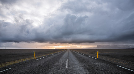 A road leading to distance at dramatic cloudy day with mountains in the background