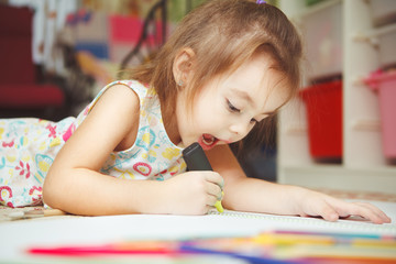 Little girl carefully draw picture in notebook with felt pen