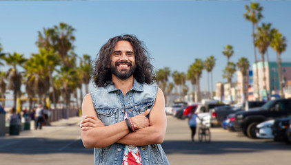 subculture, youth culture and people concept - smiling young hippie man in demin vest over venice beach in los angeles background