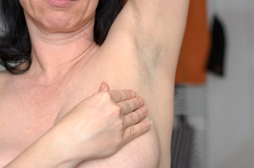 Naked woman doing a breast self examination