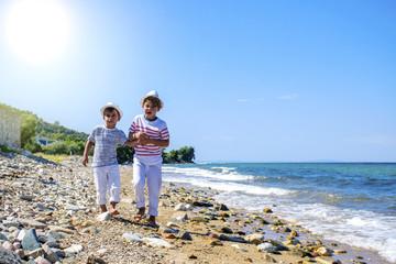 Two happy little boy  running at beach