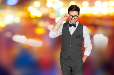 fashion, style and vintage concept - happy man in festive suit and eyeglasses over night city lights background