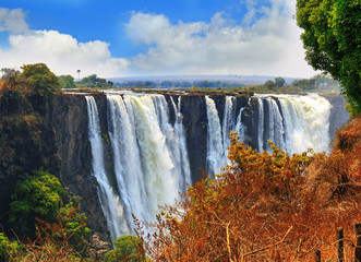 Victoria Falls taken from the Zimbabwe side overlooking Zambia, with a blue cloudy sky and gushing falls