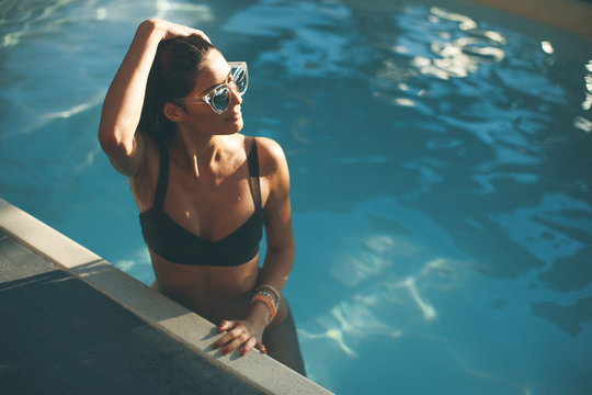 Young slim woman relaxing by swimming pool