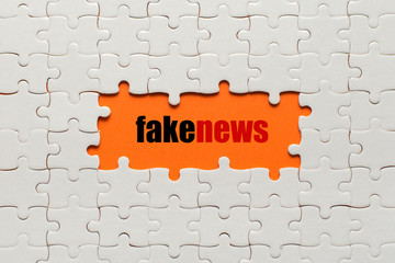 Wall Mural - White details of puzzle on orange background and word fake news
