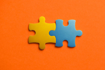 Wall Mural - Two colored details of puzzle on orange background, Yellow and Blue, close up