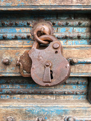 Old rusty padlock in the closed position, hanging on a dilapidated wooden door
