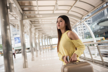 Attractive woman with luggage. Travel aboard