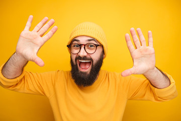 Excited bearded man with hands up