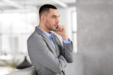 business people, technology and corporate concept - businessman calling on smartphone at office