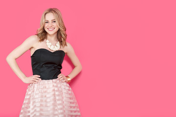 Attractive blonde young woman in elegant party dress and golden jewelry. Girl posing on a pastel pink background. Fashion photo.