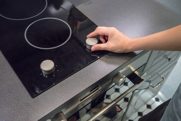 Woman's Hands adjusting temperature button on oven