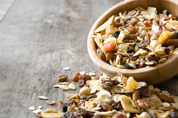 Muesli and dried fruit in wooden bowl on wooden table. Copyspace