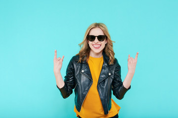 Crazy beautiful rock Girl in leather jacket and black sunglasses. Punk is not dead. Attractive cool young woman making horn sign hand gesture.