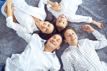 Happy family smiling lying on the floor. View from above.